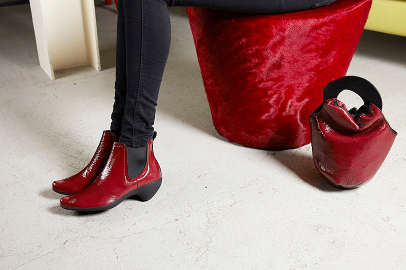 Tracey Neuls red patent heeled shoes red loop  bag and red chair  on black floor in Elementary store Shoreditch Redchurch Street