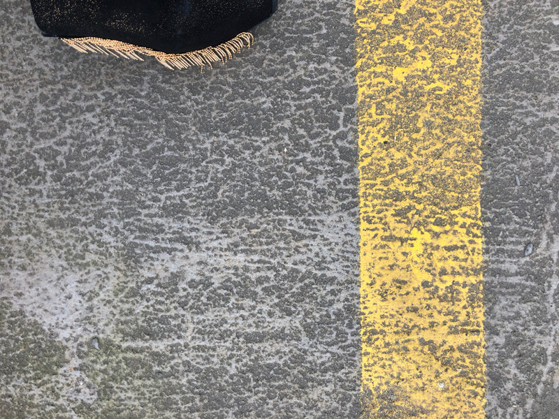 a detail of gold fringed black designer ankle boot against the concrete and yellow line of a road