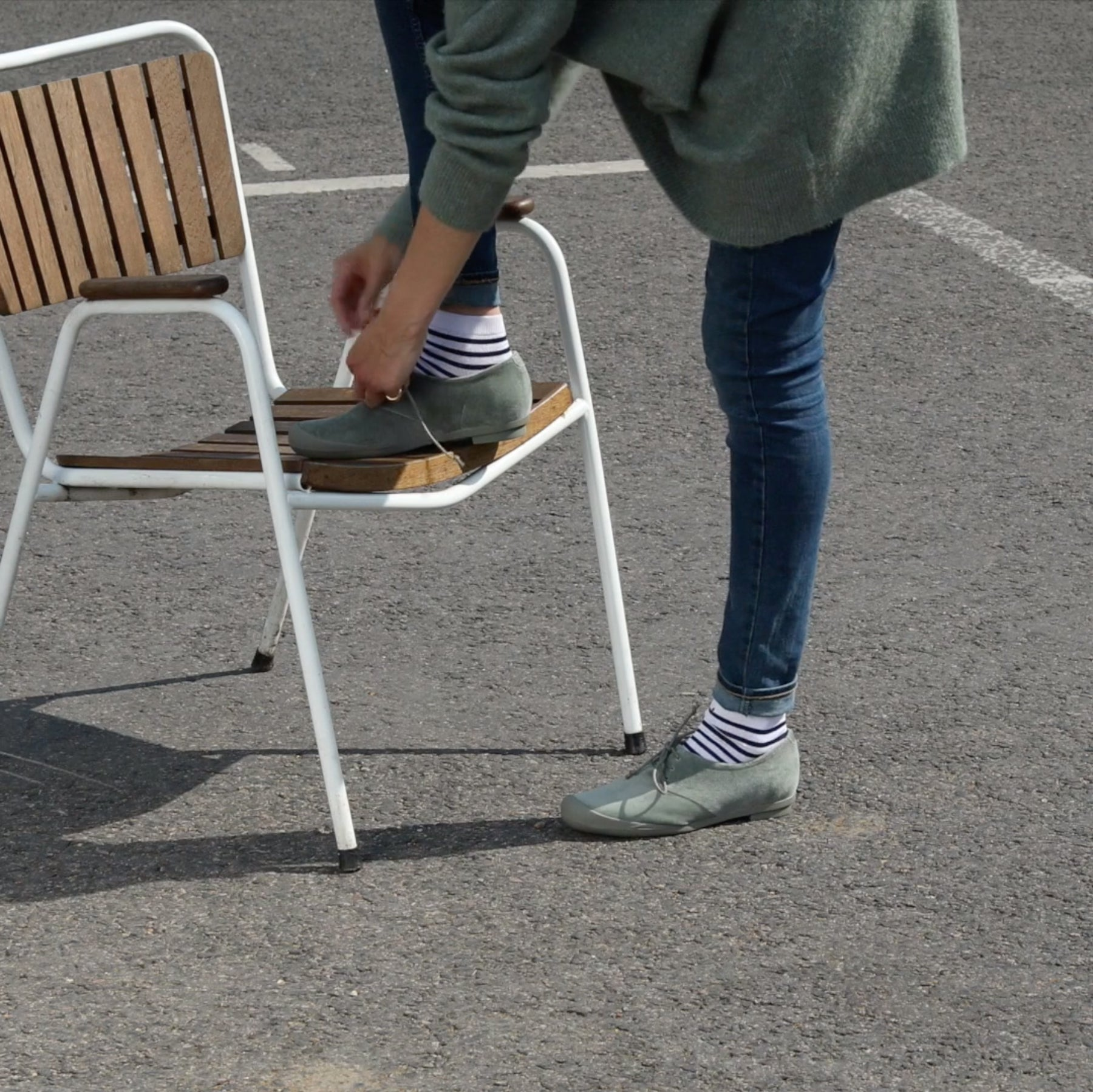 Model wears grey velvet brogues with stripy sailor socks, on a grey asphalt ground.