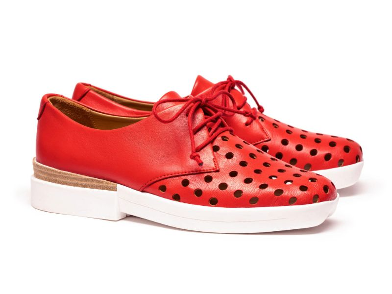 A pair of women's luxury brogue lace up shoes in tomato red with white soles, by designer Tracey Neuls