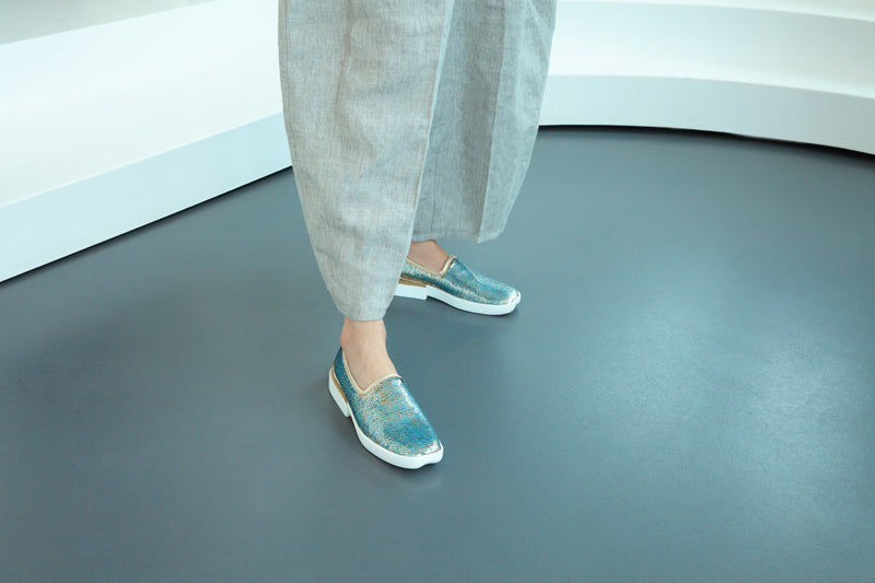 Silver sparkly shoes with linen trousers on a grey floor