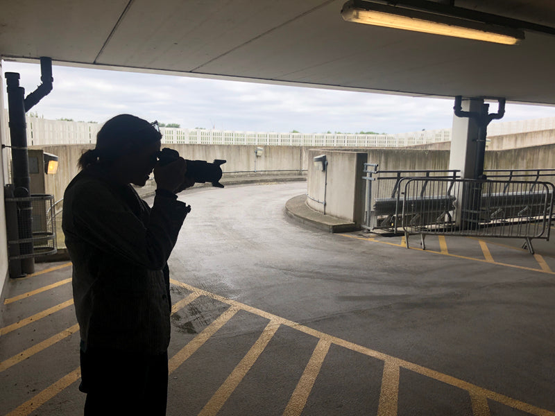 Female photographer in black, pointing her camera on a shoot in a multi-storey carpark