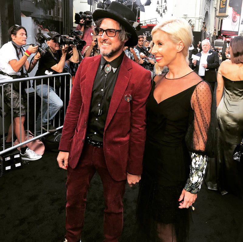 Man in red suit with glamorous wife on red carpet for film premiere