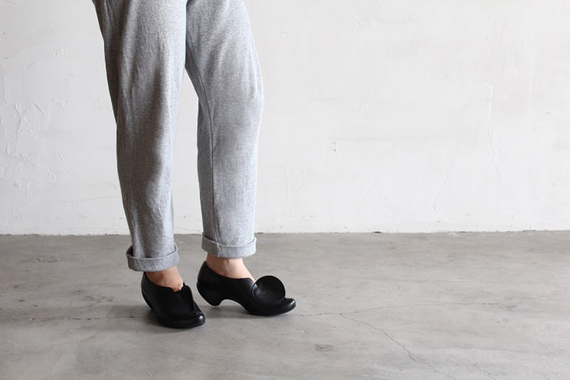 some grey trousers with a grey floor and black shoes