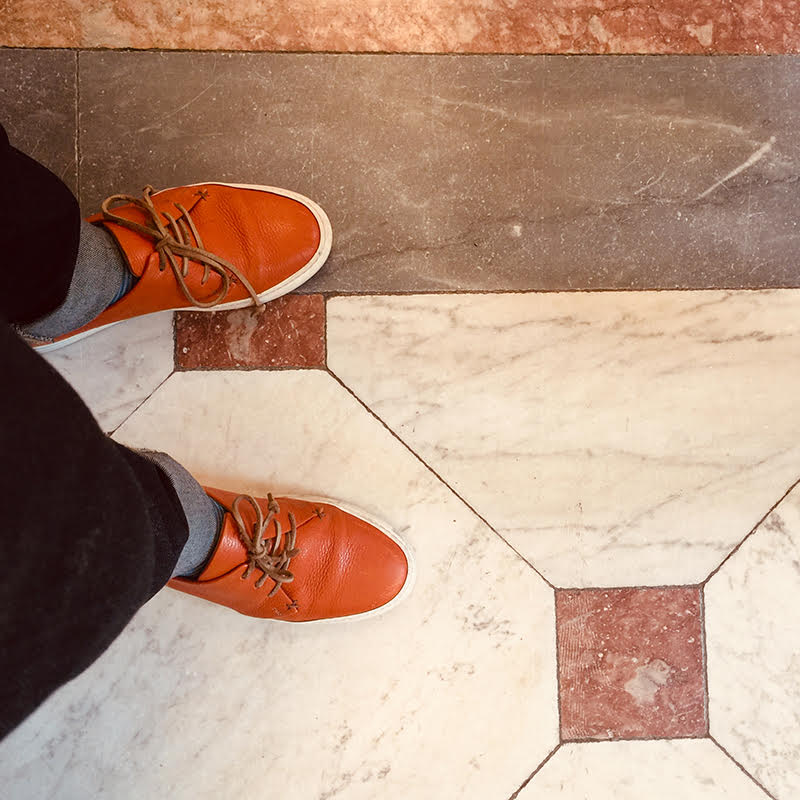 overhead shot of man wearing Karl leather sneaker in persimmon designed by Tracey Neuls