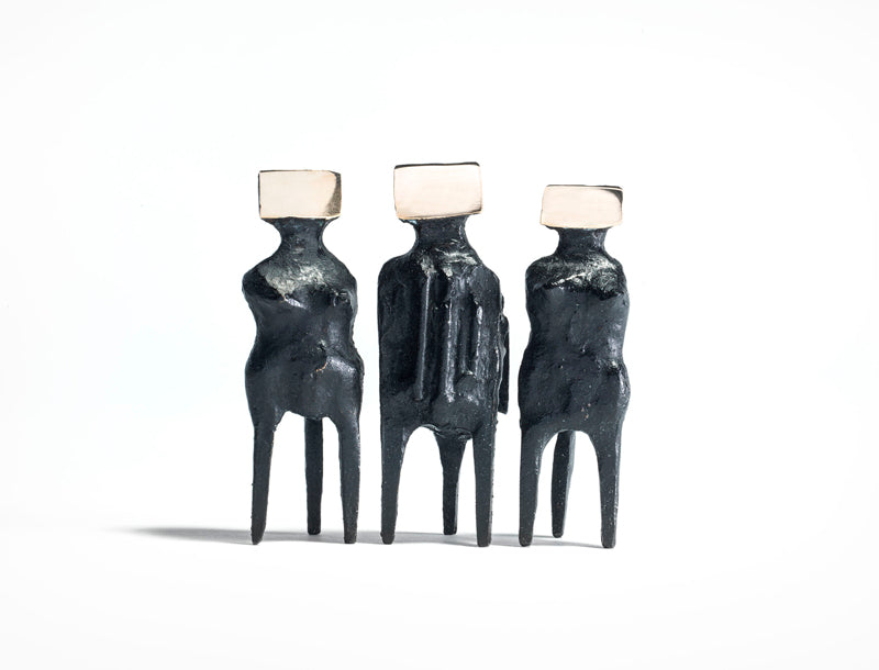 Sculpture of three black figures with white cube heads by artist Lynn Chadwick
