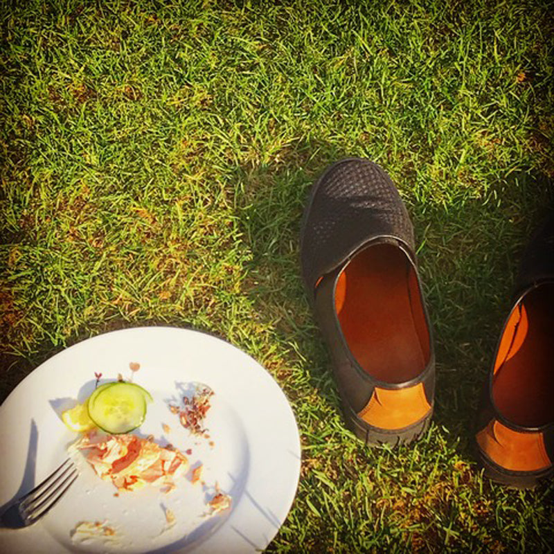 A plate of leftovers on a lawn in Summer, next to a pair of slip on men's shoes