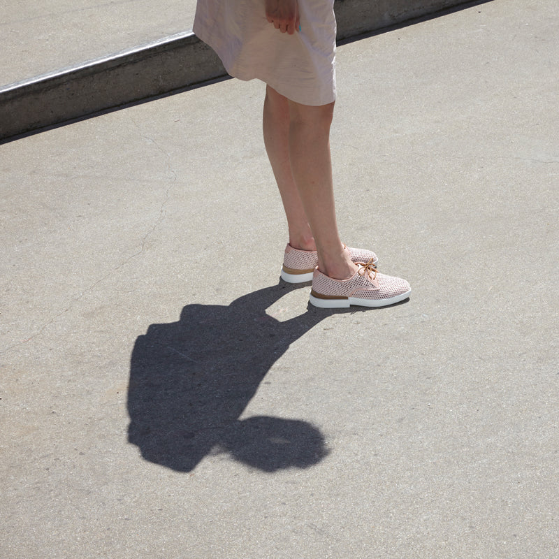 girl in pink dress and pink trainer shoes with silhouette shadow