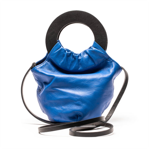 Blue leather handbag with circle handle and shoulder strap by designer Tracey Neuls