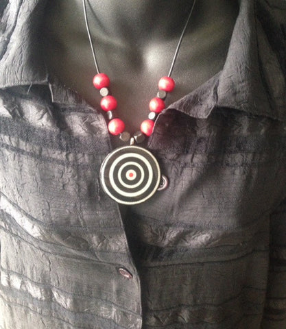 Black and white bull's eye pendant with red beads from www.andreaandme.com