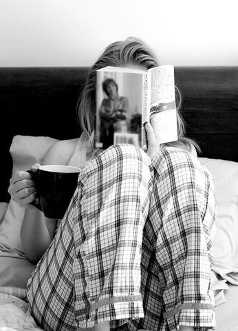 girl reads book with hello tea in bed