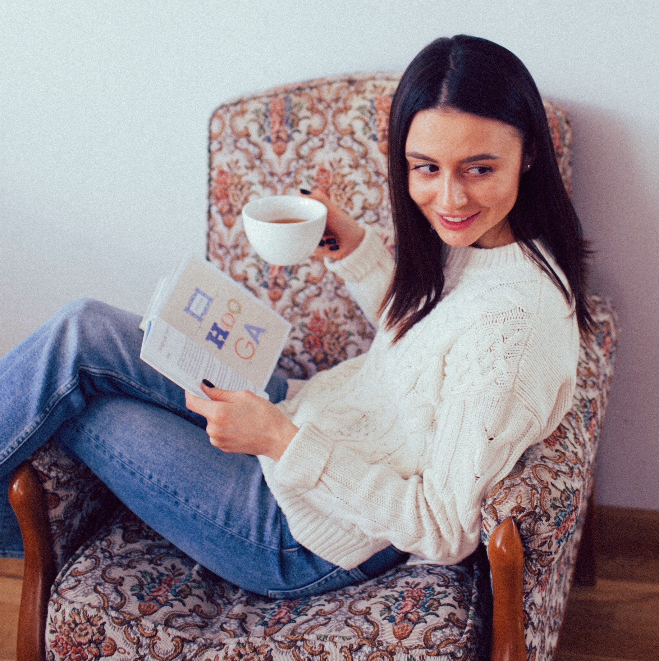 girl seating in the chair holding a book in one hand and a cup of tea in another