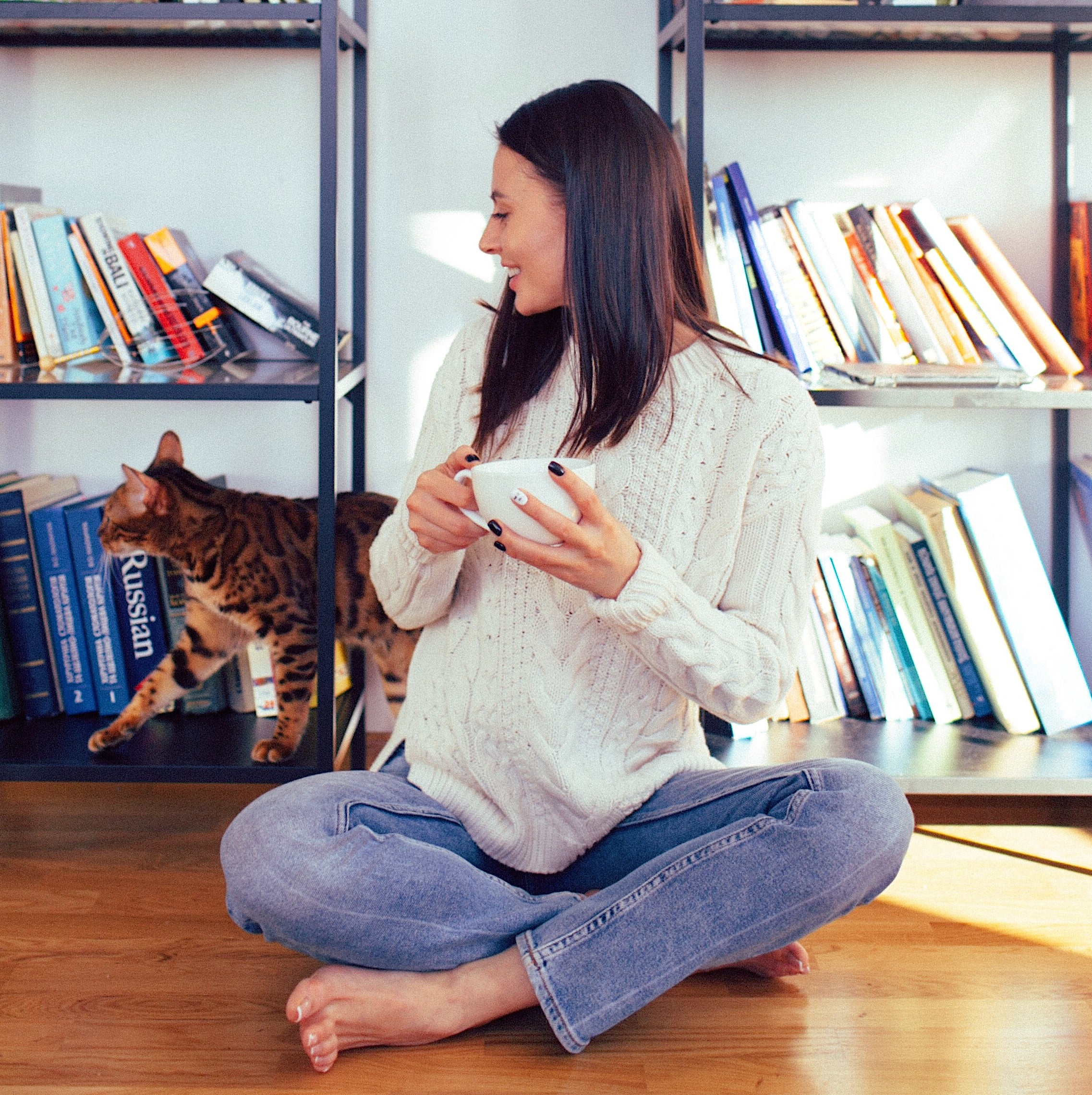 girl seats in front of the book shelf holding a cup of tea in her hands looking on the cat that is next to her