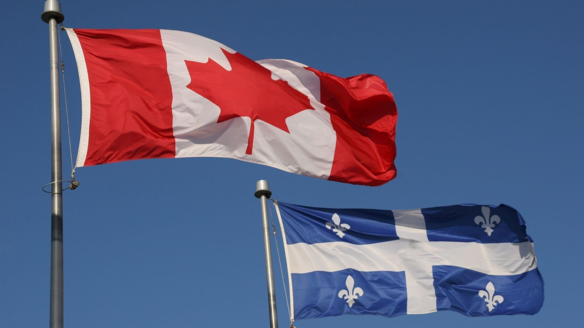 canadian ans quebecer flags waving in the blue sky