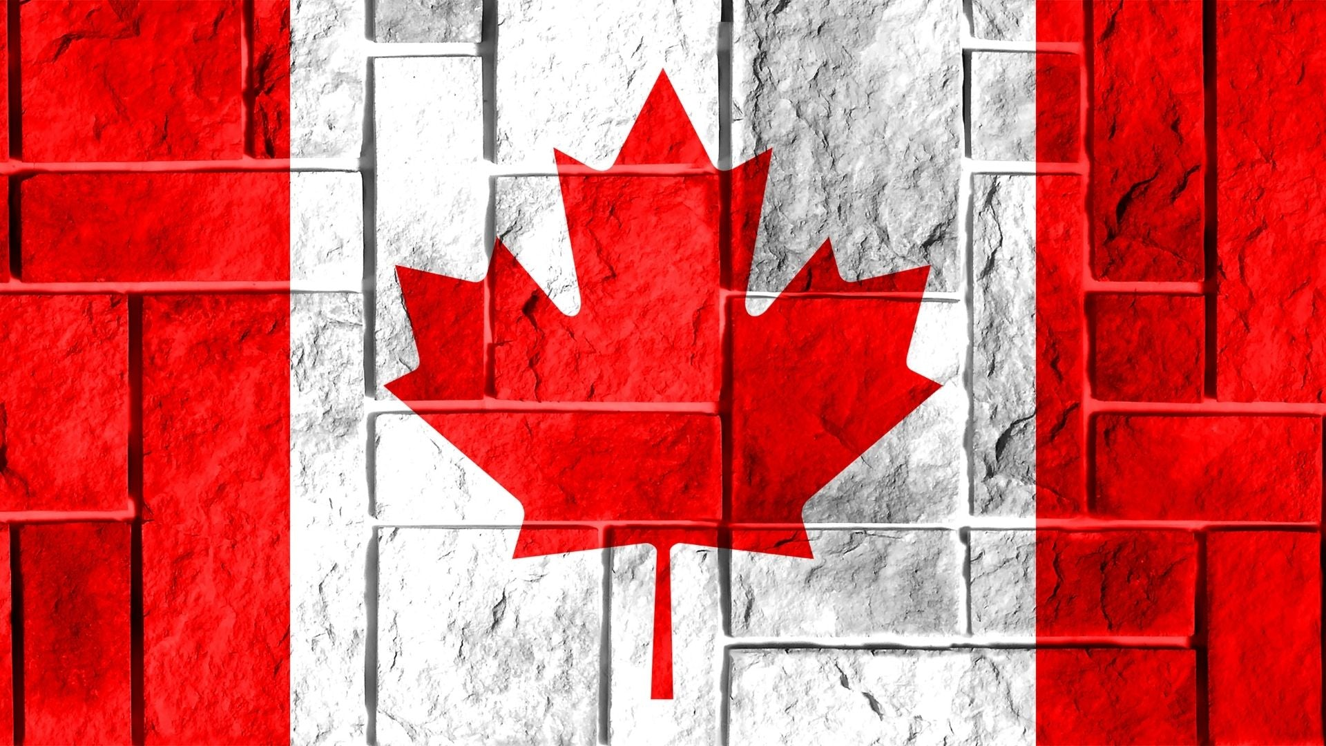 A Canadian flag painted on a white brick wall