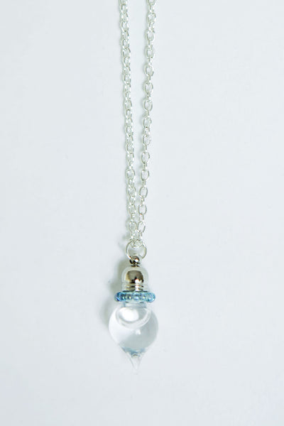 Handmade glass pendant containing holy water on a silver chain with blue edging