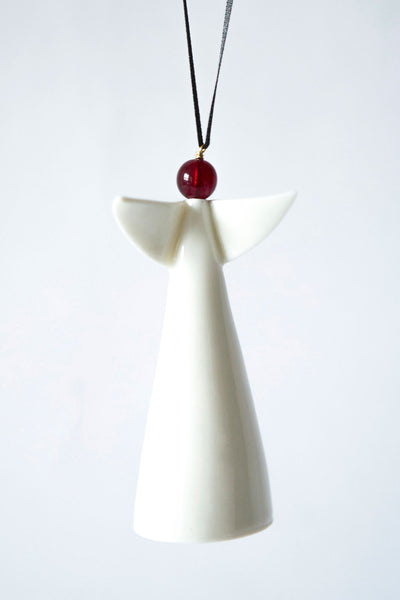 Irish ceramic angel with white body and wings and red head suspended on black hanging