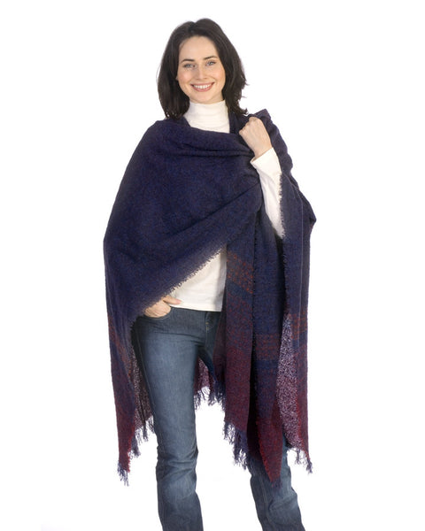 A smiling women wears the Blueberry wine Celtic Ruana with dark purple and pink hues in Irish wool
