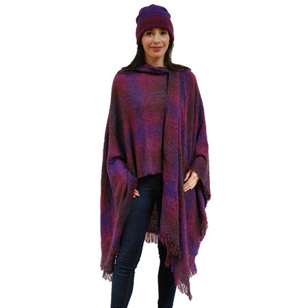 A woman wears the Wild berry Celtic Ruana in superfine irish lambswool with hues of pink, red and purple with a matching hat
