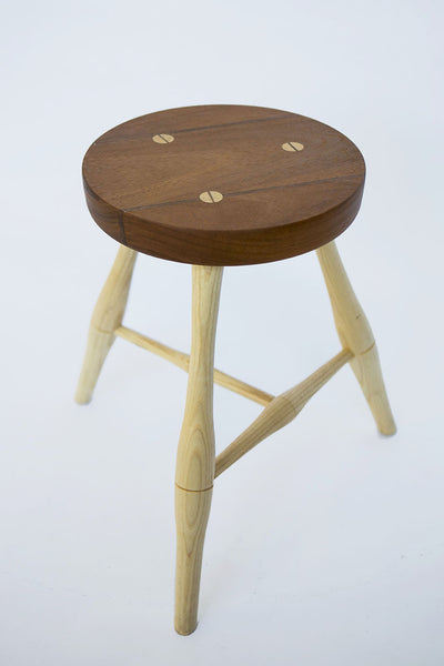 Low carved milking stool with three legs, in traditional irish style