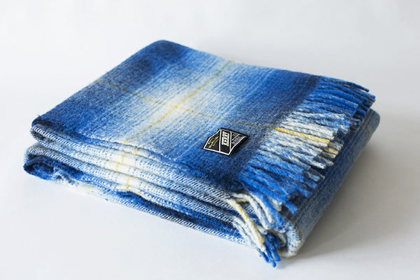 Folded Irish wool blanket with blue checkered pattern and visible label