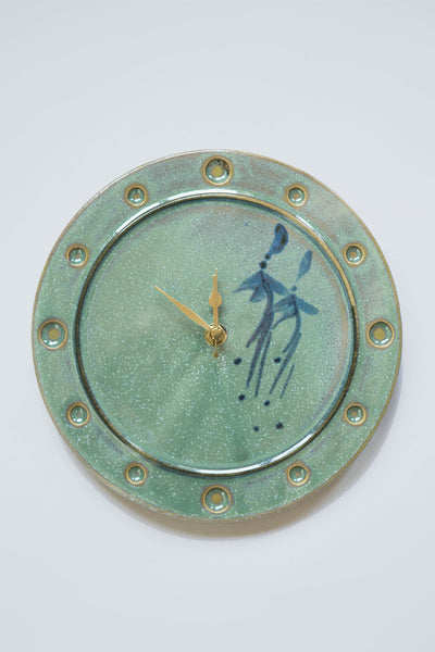 Irish green ceramic clock with two blue fuchsia flowers on the right half and brass hands