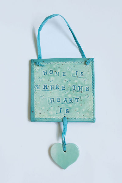 "Gift your home this square green Irish stoneware wall-hanging with blue letters saying ""Home is where the heart is"""