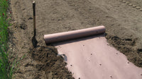 A roll of brown pre-punched paper mulch being laid onto the soil and over the ground