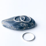 three polished silver rings on a rock