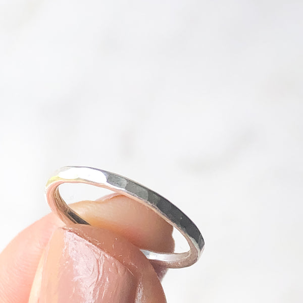 Hammered textured stacking ring held up between a thumb and fore finger