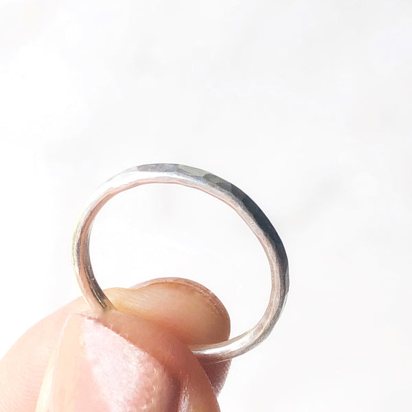 Another view of a single stacking ring being held between a thumb and fore finger