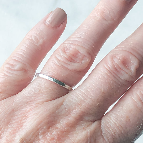 a single silver stacking ring being worn on a ring finger