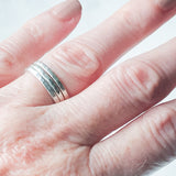 a trio of hammered silver stacking rings being worn