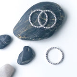 sterling silver beaded stacking rings on a rock