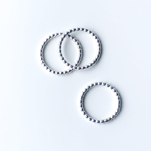 Three silver stacking rings with beaded texture