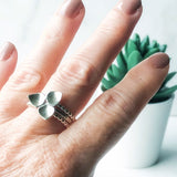 Silver trillium ring worn with two beaded silver stacking rings