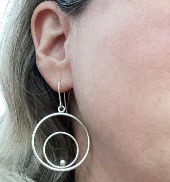 Silver circles hoop earrings on model