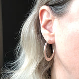 Large silver boho textured hoops on model