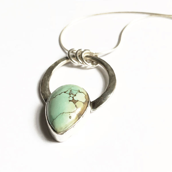 Tear drop turquoise from treasure mountain in a silver circle pendant