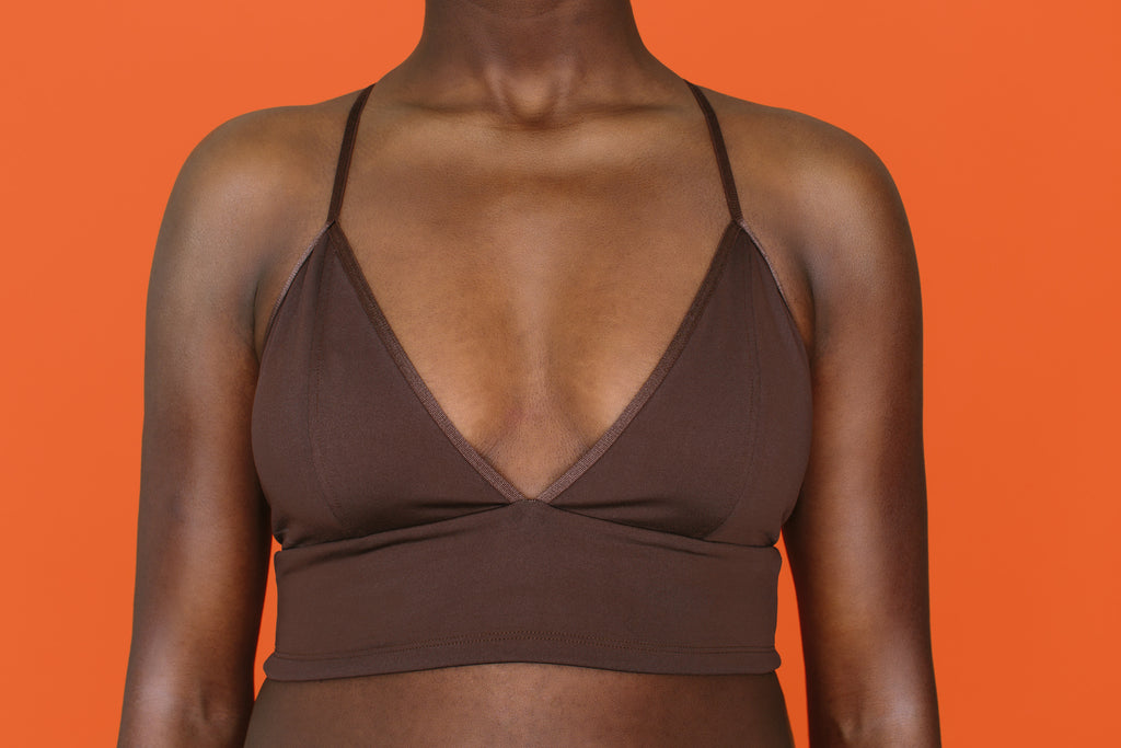 Front view of Proclaim T-Back Bralette (racerback wireless unpadded style) in Nude Nina color. Made out of recycled plastic bottles (recycled polyester)