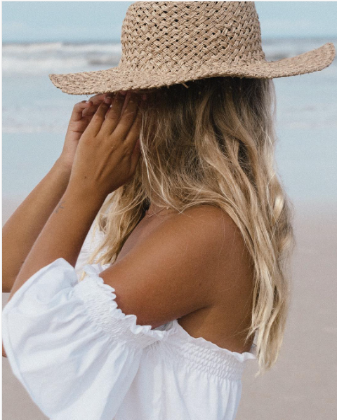 Blonde girl with hat on on beach
