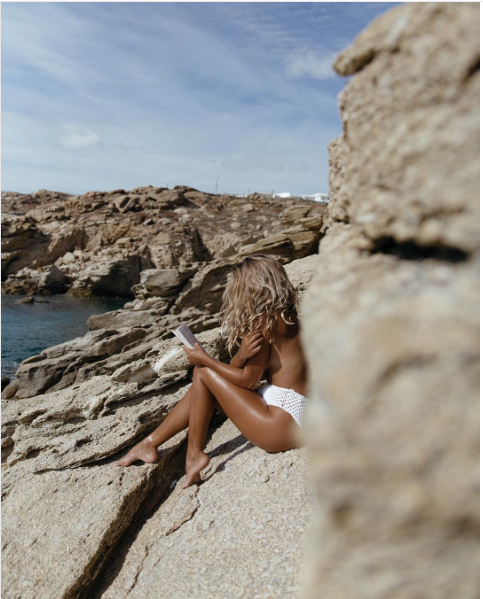 Tanned girl sits on rocks