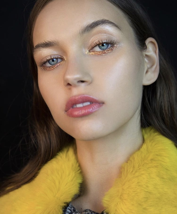 Brunette with gold under eye, highlighter and bold yellow top