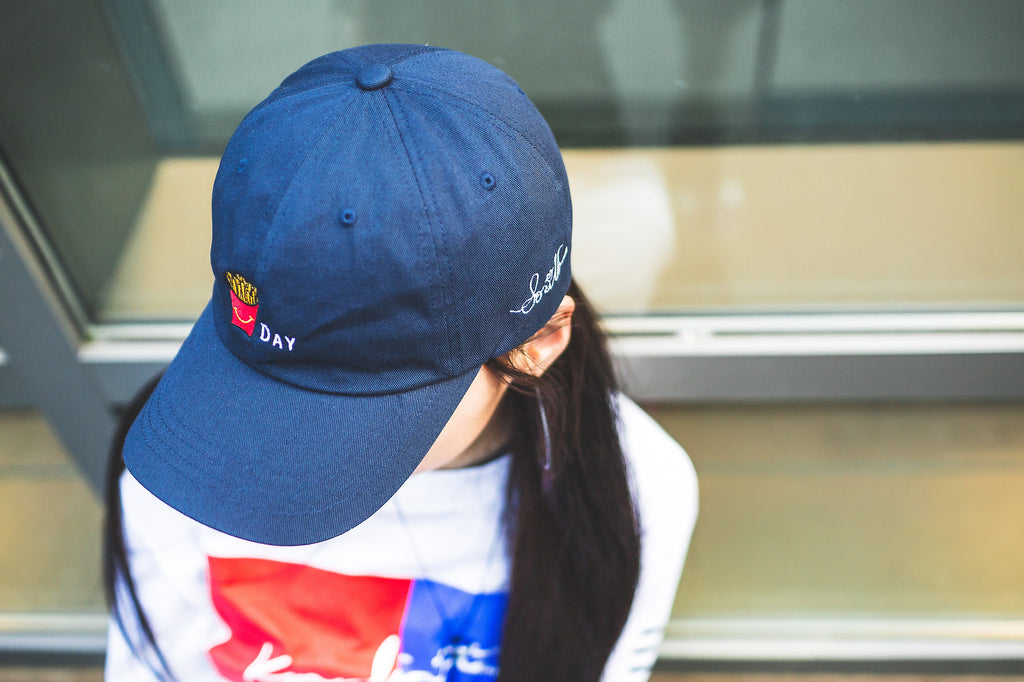1 Million Dance Studio choreographer Sori Na wearing KORE x Sori Na's FryDay dad hat in navy and KOREATOWN 90 long sleeve in white.