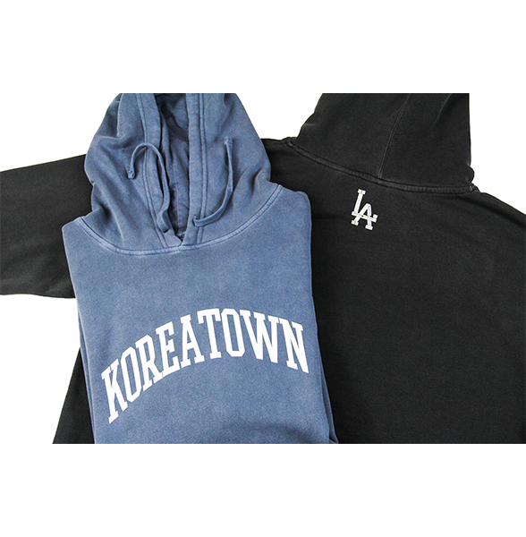 Laid out shot of front view of washed slate hoodie and back view of washed black hoodie.