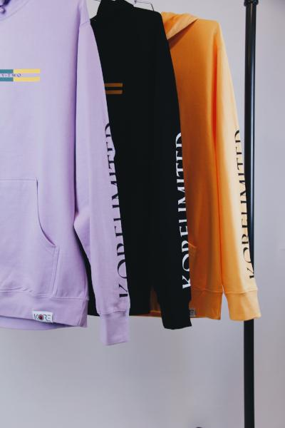Lavender, peach, and black pullover Goryeo hoodies hanging on black rack. KORE Limited - Keepin Our Roots Eternal