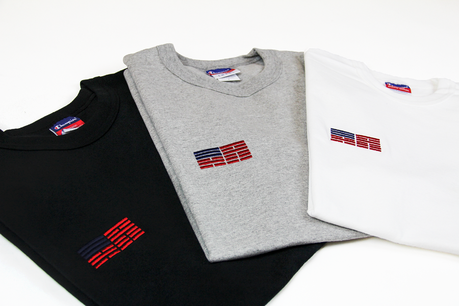 Black, heather grey, and white KR-AM Champion jersey tee folded.