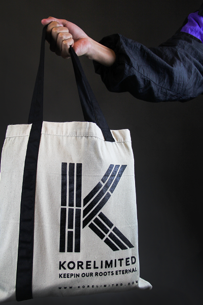 Male model holding up the KORELIMITED canvas tote bag with trigram K logo showing on the front along with the website www.korelimited.com.
