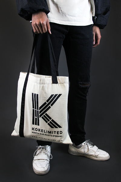 Male model holding the KORELIMITED canvas tote bag with the front showing. Trigram K logo is printed on the front along with the website www.korelimited.com.