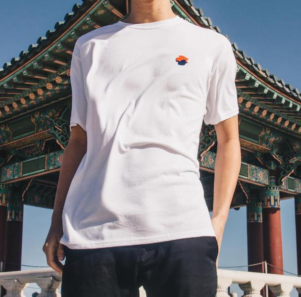 Front shot of model wearing white Made in Korea tee in front of Friendship Bell.